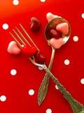 Cuillère et fourchette avec des sucreries de coeur de Valentine Photo libre de droits