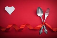 Cuillère et fourchette de vintage avec un coeur de service et blanc pour le jour du ` s de Valentine sur un rouge Photographie stock libre de droits