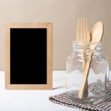 Cuillère et fourchette en bois avec le verre photographie stock libre de droits