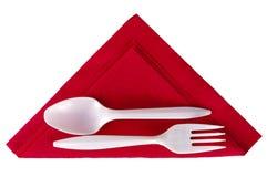 Cuillère et fourchette en plastique sur la serviette rouge de triangle Images stock