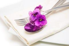 Cuillère et fourchette sur une serviette avec la fin de violette vers le haut Photographie stock