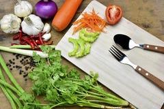 Cuillère et légumes organiques sains sur un fond en bois Photos stock