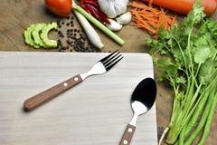Cuillère et légumes organiques sains sur un fond en bois Images stock