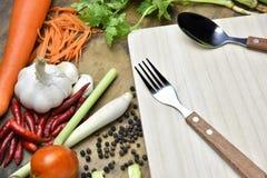 Cuillère et légumes organiques sains sur un fond en bois Photographie stock