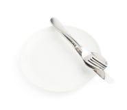 Cuillère, fourchette et couteau au-dessus du plat blanc images stock