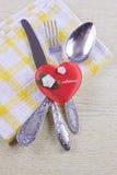 Cuillère, fourchette et couteau de Flatwares avec un coeur rouge Image stock