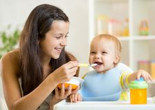 Cuillère heureuse de mère alimentant son enfant de bébé photographie stock libre de droits