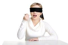 Cuillère les yeux bandés de fixation de femme avec la pile des pillules Image stock