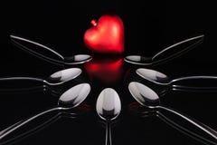 Cuillères à café et symbole d'amour sur la table en verre noire Image libre de droits