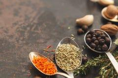 Cuillères avec des herbes et des épices sur la vieille table foncée Images libres de droits