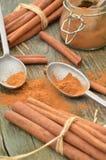 Cuillères d'étain de poudre d'épice de cannelle et bâtons de cannelle moulus Photographie stock libre de droits