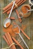 Cuillères d'étain de poudre d'épice de cannelle et bâtons de cannelle moulus Photos stock