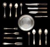 Cuillères de cru, couteaux, fourchettes et un plat d'isolement sur un fond blanc photographie stock libre de droits