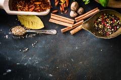 Cuillères en bois avec des épices et des herbes Photos stock