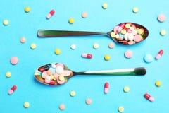Cuillères et différentes pilules Photographie stock libre de droits