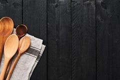 Cuillères et dishtowel en bois sur le fond en bois noir photographie stock libre de droits