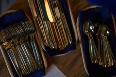 Cuillères et fourchettes d'or de couteaux dans le plateau en bois sur la table Photos libres de droits