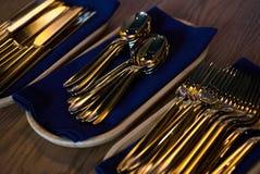 Cuillères et fourchettes d'or de couteaux dans le plateau en bois sur la table Photographie stock