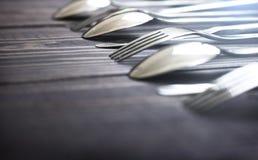 Cuillères et fourchettes en acier dans une rangée sur une table Images libres de droits