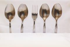 Cuillères et fourchettes sur un fond blanc Photos stock