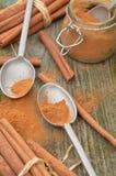 Cuillères moulues d'étain de poudre d'épice de cannelle, pot, bâtons de cannelle Photographie stock