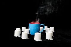 Cuisant la tasse à la vapeur de café entourée avec le fond noir de cosses de café image stock