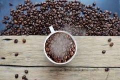 Cuisant la tasse à la vapeur de café complètement des grains de café dans la table en bois de vintage avec les haricots dispersés photographie stock