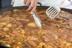 Cuiseur déplaçant le repas de Jumbalaya dans une grande casserole de Paella Photographie stock