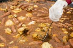 Cuiseur déplaçant le repas de Jumbalaya dans une grande casserole de Paella Images stock