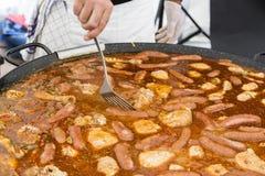 Cuiseur déplaçant le repas de Jumbalaya dans une grande casserole de Paella Image libre de droits