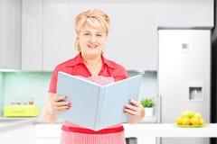 Cuiseur femelle mûr de sourire tenant un livre des recipies et du posi Images stock