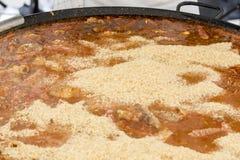 Cuiseur mettant le riz dans le repas de Jumbalaya dans une grande casserole de Paella Photos stock