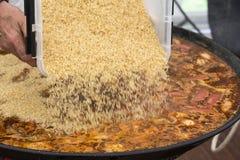 Cuiseur mettant le riz dans le repas de Jumbalaya dans une grande casserole de Paella Photos libres de droits