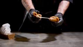 Cuiseur professionnel de chef dans les coupures noires de gants dans deux morceaux de petit pain grillé frit chaud savoureux de f clips vidéos