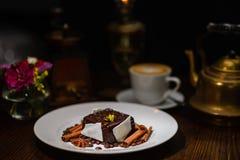 Cuisine élevée, dessert de chocolat avec des bâtons de cannelle, à l'arrière-plan par tasse de café et de fabricant de café Images stock
