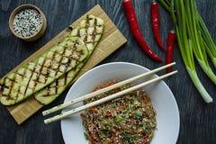Cuisine asiatique Salade des nouilles de cellophane, frite avec des l?gumes, d?cor?s des verts et des b?tons de crabe Funchoza ap photos stock