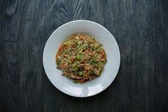 Cuisine asiatique Salade des nouilles de cellophane, frite avec des l?gumes, d?cor?s des verts et des b?tons de crabe Funchoza ap photos libres de droits