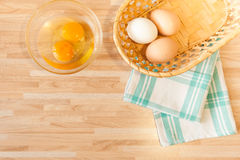 Cuisine background. Eggs in braided bucket on towel and raw eggs in glass pialat on light wooden background with copyspace. Cuisine background Royalty Free Stock Images