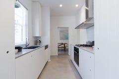 Cuisine blanche rénovée de style d'office en appartement moderne Image libre de droits