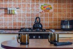 Cuisine, bouilloire et deux tasses vides images libres de droits