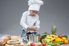 Little Boy Crashing Fresh Egg In Cooking Hat. Stock Photos