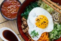 Cuisine coréenne, Bibimbap de boeuf dans un pot d'argile dessus photographie stock libre de droits