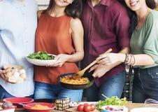 Cuisine d'amis faisant cuire dinant le concept d'unité Image libre de droits