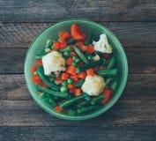 Cuisine d'Asiatique de plat mélange végétal des carottes, des pois, des haricots verts et du chou-fleur dans une cuvette verte Image stock
