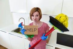 Cuisine de femme à la maison dans les gants avec le balai et le balai de nettoyage demandant l'aide photos libres de droits