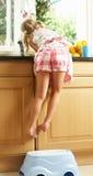 Cuisine de fille aidant avec laver vers le haut images libres de droits