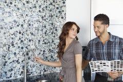 Cuisine debout de maison modèle de beaux jeunes couples avec des échantillons de couleur Images stock