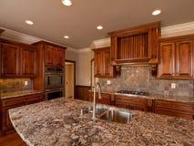 Cuisine en bois foncée à la maison de luxe avec la partie supérieure du comptoir Images stock