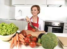Cuisine heureuse de femme à la maison préparant la salade végétale avec de la laitue, carottes et découpant le sourire en tranche Photographie stock libre de droits