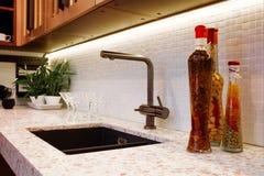 Cuisine intérieure, bouteilles en verre avec du maïs, écrous, huile, confiture dans une cuisine moderne avec un mélangeur de luxe Image libre de droits